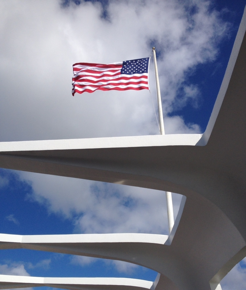 The American flag flying over the USS Arizona Memorial