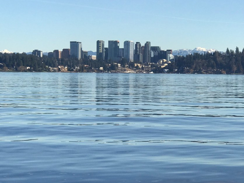 The Bellevue city skyline reflected in Lake Washington; the North Cascades visible in the background.